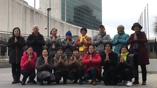 在联合国大厦前讲法轮功真相的部分法轮功学员恭祝李洪志师父新年快乐。(纽约法轮功学员提供)