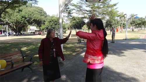 '图8:现年八十几岁的蔡老太太(左),巧遇法轮功集体活动,她走近了炼功队伍,展开双臂跟着学炼,旁边学员热心的教她炼功。'